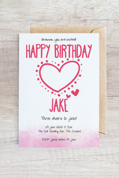big pink heart invitation placed on top of envelope