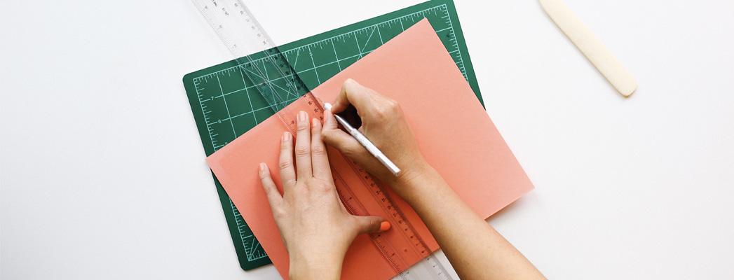 cutting a paper in half on a cutting mat
