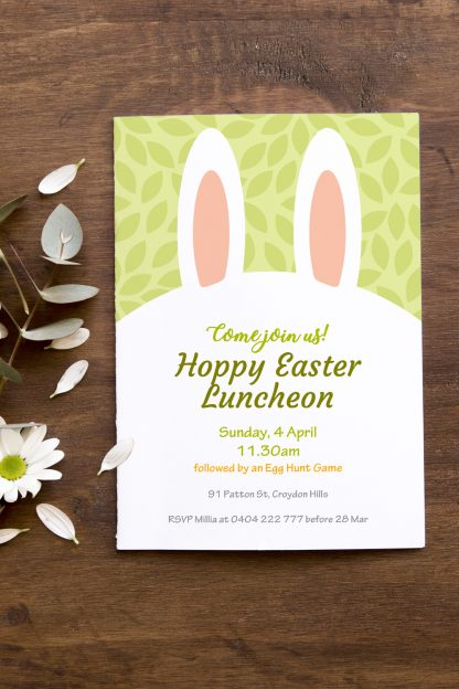 spring green easter bunny ears invitation flat lay with white flowers